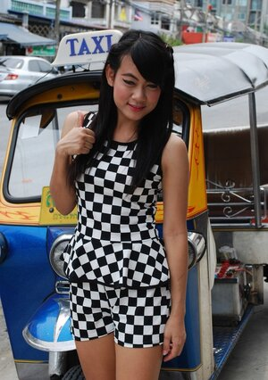 Inviting Thai performer in a checkered dress gets into the Tuk Tuk Taxi