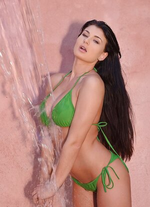Lady in green bikini enjoys water falling down on her body in the street