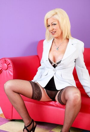 Old blonde Sindi Star demonstrates her nice-looking body on the sizeable red sofa