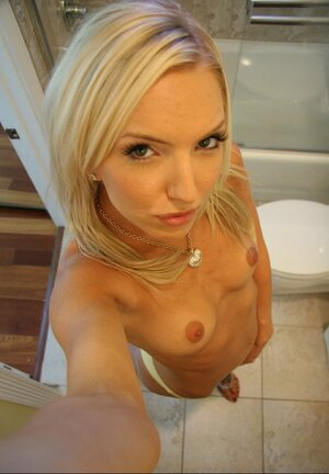 Underweight blonde seductively poses on camera during solo fun in bathroom
