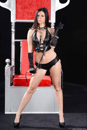 BDSM posing of excited woman with small breasts who holds a stick in her hands